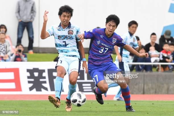 Park Riki of FC Ryukyu and Tsubasa Terayama of FC Tokyo compete for the ball during the J.League J3 match between FC Tokyo U-23 and FC Ryukyu at...
