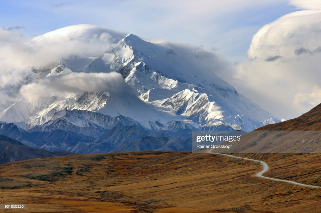 Park road in autumn landscape leading toward majestic Mount Denali : Stock-Foto