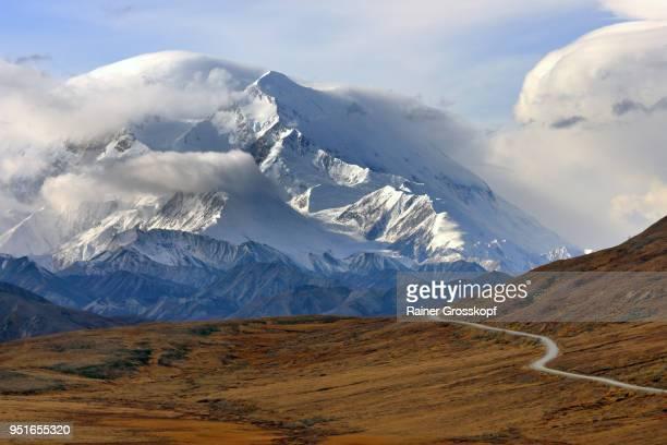 Park road in autumn landscape leading toward majestic Mount Denali