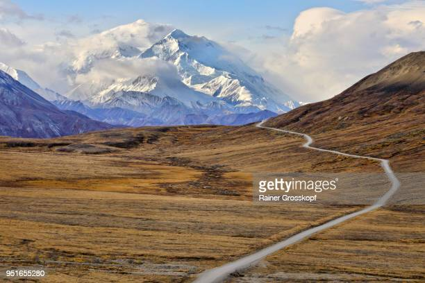 Park road in autumn landscape leading toward Mount Denali