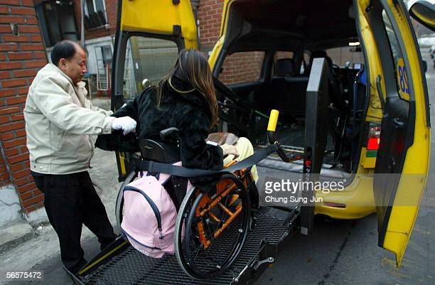 Park Sang-Hee, who is spinal cord injury patient, alights from an adapted taxi on January 12, 2006 in Seoul, South Korea. More than 130,000 spinal...