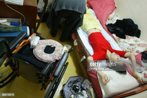 Park Sang-Hee, who is spinal cord injury patient, exercises at home with the help of her mother on January 12, 2006 in Seoul, South Korea. More than...