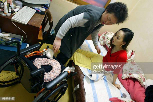 Park Sang-Hee, who is spinal cord injury patient, is assisted at home by her mother on January 12, 2006 in Seoul, South Korea. More than 130,000...