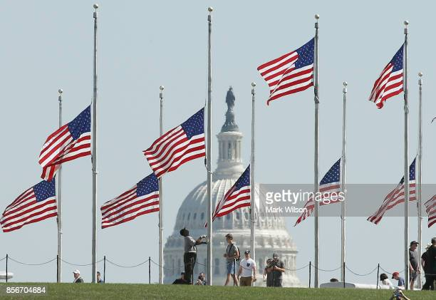 Park Service employee lowers the US flags on the grounds of the Washington Monument to halfstaff on October 2 2017 in Washington DC President Donald...