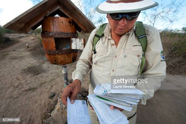 Park Service Guide Javier Cando looks through mail at Floreana Island