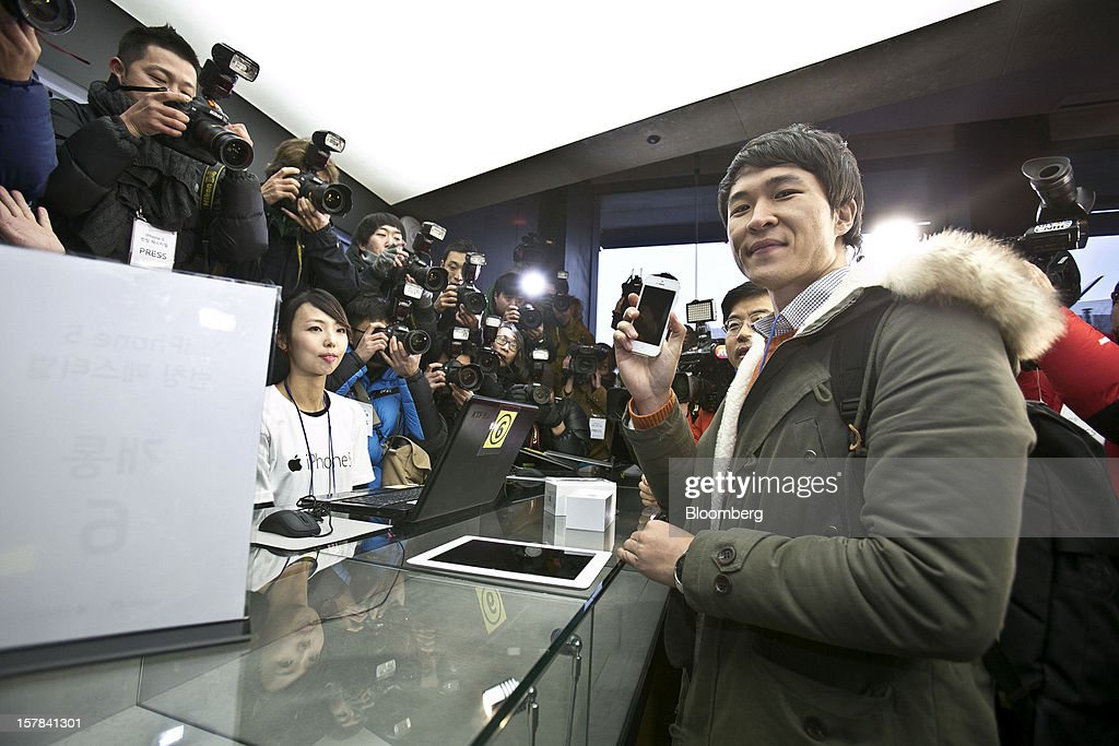 Park Seul-gi, 27, first in the queue for Apple Inc.'s iPhone 5, poses for photographs after purchasing the device at a KT Corp. Olleh brand mobile phone store in Seoul, South Korea, on Friday, Dec. 7, 2012. The iPhone 5 went on sale in South Korea today. Photographer: Jean Chung/Bloomberg via Getty Images