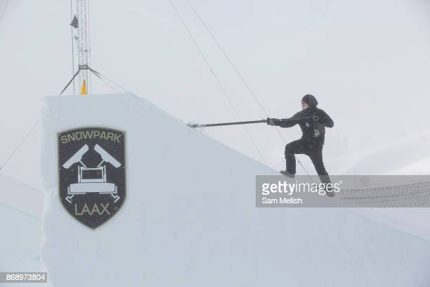 A park shaper scraps snow from a jump for the Laax Open on 17th January 2017 in Laax Switzerland The Laax Open is a FIS Snowboarding World...