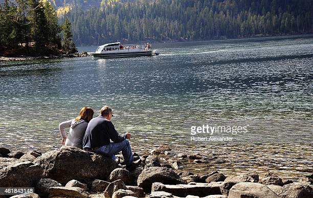 Park visitors sit on rocks beside Jenny Lake as an excursion boat returns to the dock in Grand Teton National Park in Wyoming