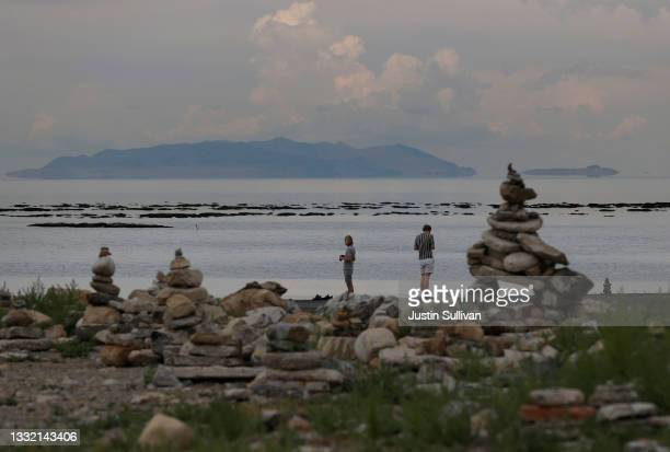 Park visitors stand on the banks of the Great Salt Lake at the Great Salt Lake State Park on August 02, 2021 near Magna, Utah. As severe drought...