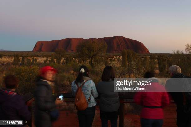 Park visitors take photos during sunrise from a viewing area at Uluru on August 14, 2019 in the Uluru-Kata Tjuta National Park, Australia. The...