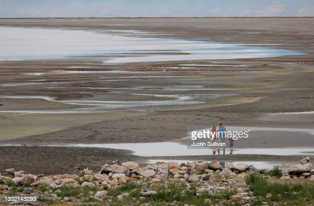 Park visitors walk along a section of the Great Salt Lake that used to be underwater at the Great Salt Lake State Park on August 02, 2021 near Magna,...