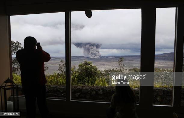 Park visitors watch as an ash plume rises from the Halemaumau crater within the Kilauea volcano summit caldera at the Hawaii Volcanoes National Park...