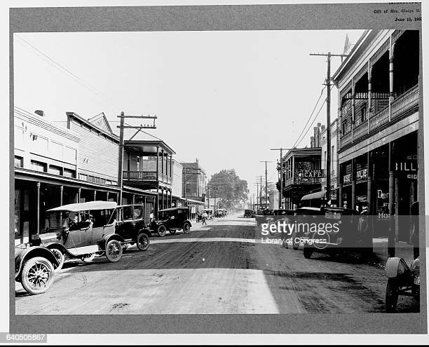 Parked automobiles line a street in the business district of Lafayette, Louisiana. In a relatively short time, mass-produced cars had replaced the...