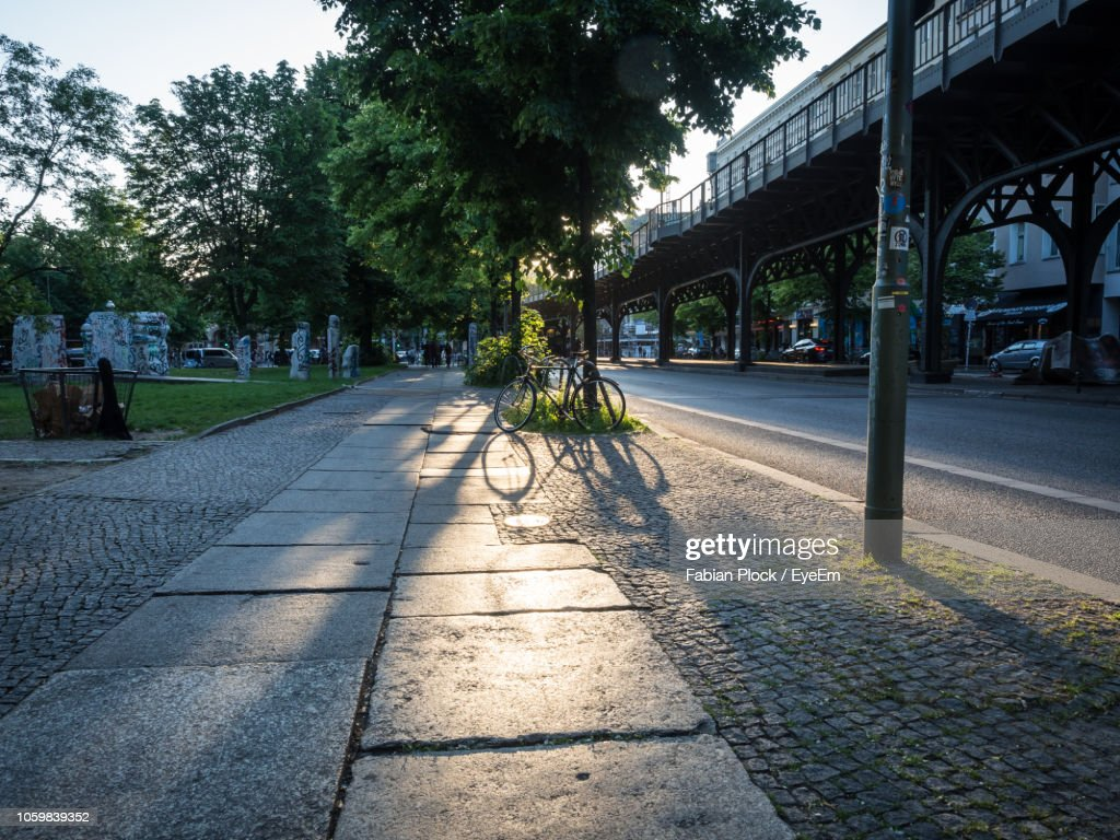 Parked Bicycle And Long Shadow On Road In Berlin Kreuzberg : ストックフォト