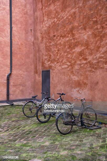 parked bikes in front of a red brick wall. - emreturanphoto stock pictures, royalty-free photos & images