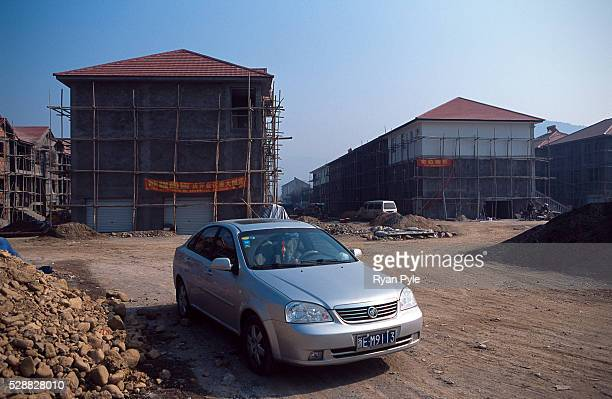 A parked car in front of new multistory homes that are part of a real estate development that has popped up over the last half year next to the King...
