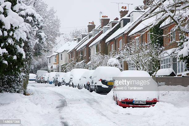 Parked cars in residential street covered in thick snow after blizzard.