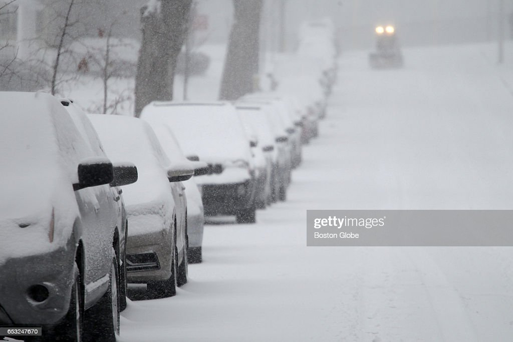 Parked cars line a snowy street in Worcester, MA as a winter storm arrives in the region on Mar. 14, 2017.