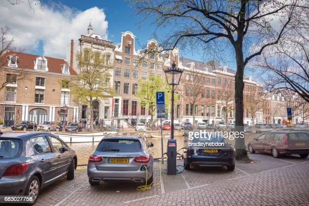 Parked electric cars charging along the canals of Amsterdam, Netherlands