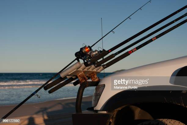 A 4WD parked on the beach with fishing rods sttached to the front of the vehicle.