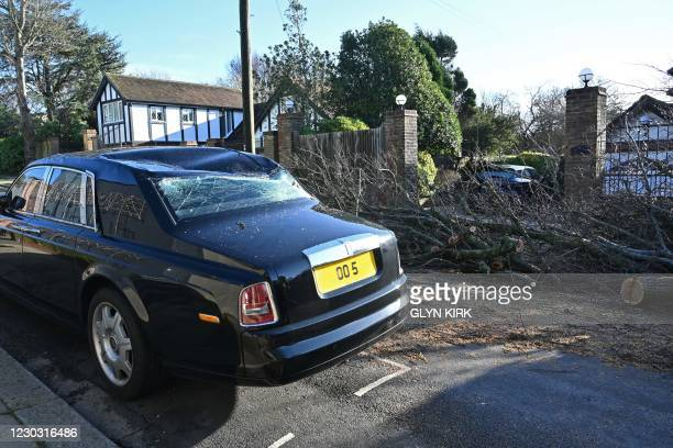 Parked Rolls Royce luxury car is seen damaged in a street in Hove after a tree comes down in the high winds on the south coast of England on December...
