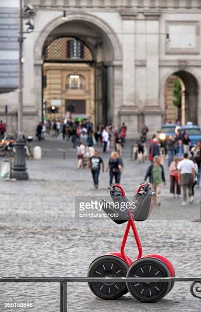 parked segways at piazza del popolo with crowds and gate at the background. - emreturanphoto ストックフォトと画像