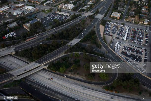 Parked vehicles sit in a lot next to a mostly empty interchange between the 101 and 405 freeways in this aerial photograph taken above Los Angeles,...