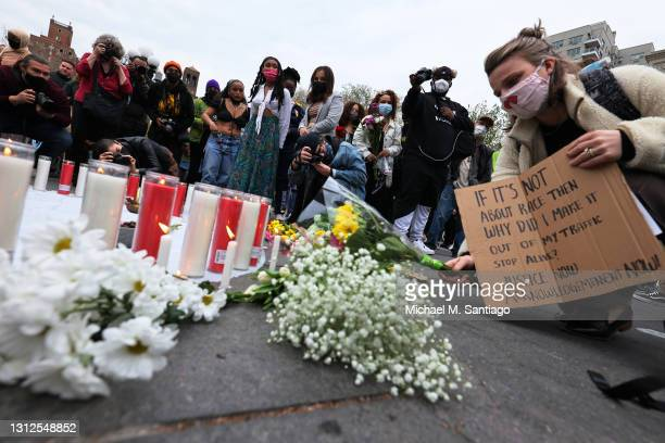 Parker Daley places flowers at a makeshift memorial during a vigil for Daunte Wright and Dominique Lucious at Washington Square Park in Manhattan on...