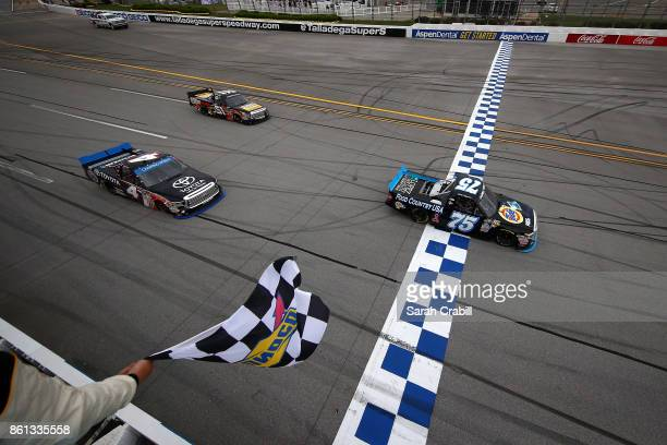 Parker Kligerman driver of the Food Country USA/Lopez Wealth Mgmt Toyota takes the checkered flag to win the NASCAR Camping World Truck Series Fred's...