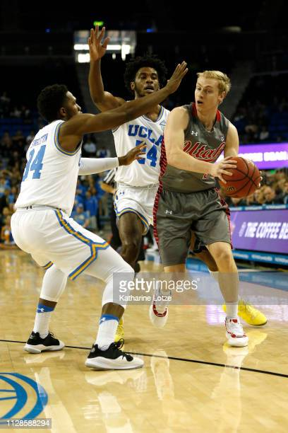 Parker Van Dyke of the Utah Utes looks for an opening as David Singleton of the UCLA Bruins and Jalen Hill of the UCLA Bruins attempt to block during...