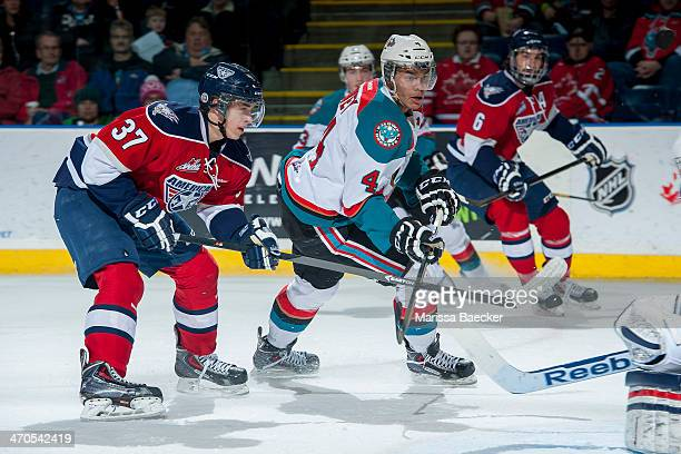 Parker Wotherspoon of the Tri City Americans checks Madison Bowey of the Kelowna Rockets as he takes a shot on net during the first period on...