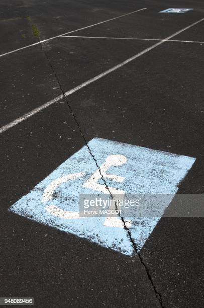 Parking access for dissabled people on a grey crackled and fissured concrete ground