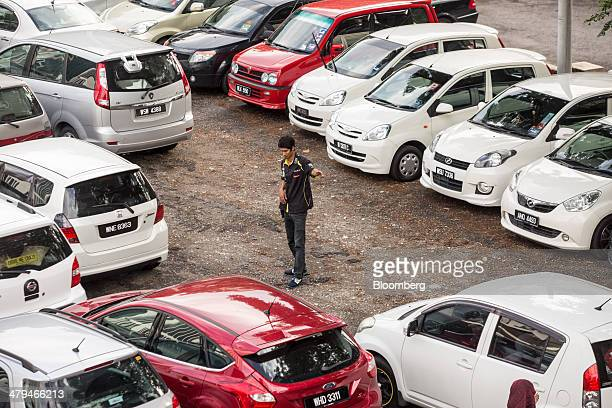 Parking attendant directs cars in a makeshift parking lot during the morning rush hour in Kuala Lumpur, Malaysia, on Tuesday, March 18, 2014....