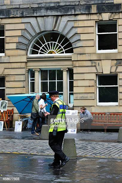 Parking attendant patrolling a city street in Edinburgh