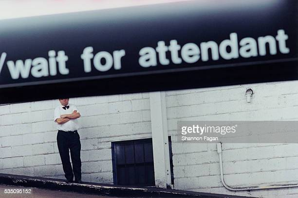 Parking Attendant Waiting Under Sign