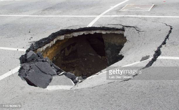 parking destroyed by the effects of rain - sinkhole stock photos and pictures