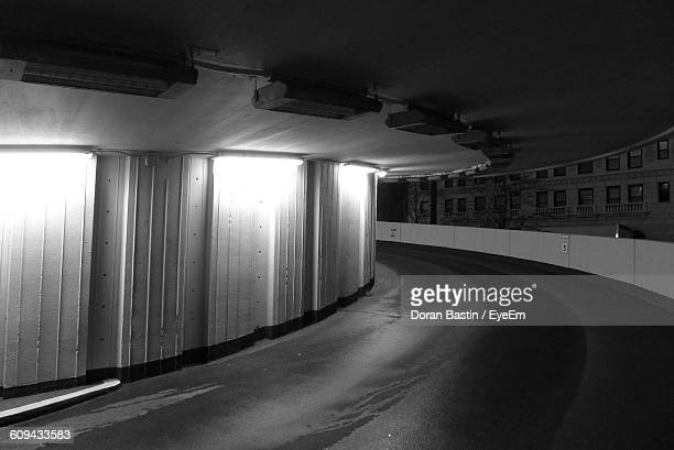 Parking Garage By Empty Road In City At Night