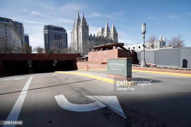 A parking garage is closed with the historic Mormon Salt Lake Temple in the background across the street from the Conference Center that sits empty...