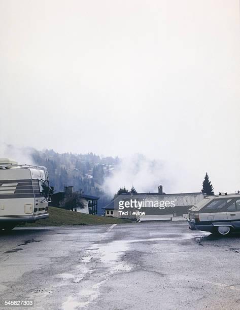 parking lot and mountain village in fog - ムジェーヴ ストックフォトと画像