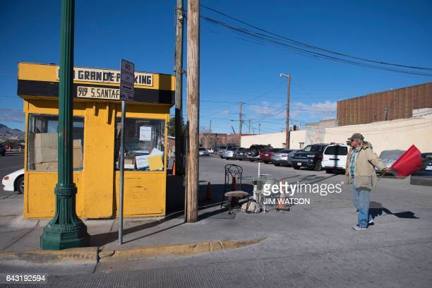 Parking lot attendant waves a red flag to cars near the Port of Entry in El Paso, Texas, on February 20, 2017. ATTENTION EDITORS: This image is part...