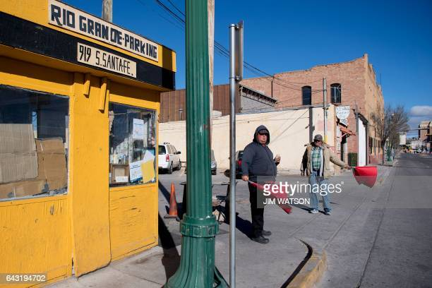 Parking lot attendants wave red flags to cars near the Port of Entry in El Paso, Texas, on February 20, 2017. ATTENTION EDITORS: This image is part...