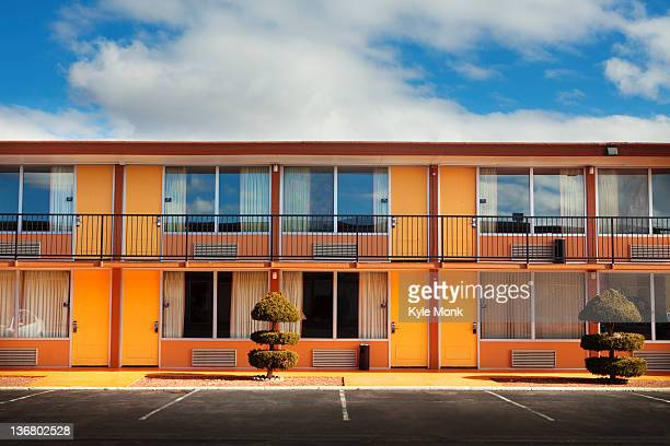 parking lot, doors and windows of motel - motel stock photos and pictures