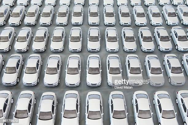 parking lot filled with brand new silver cars