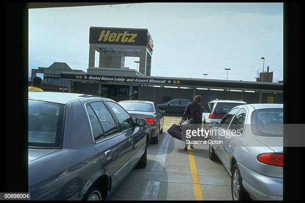 Parking lot outside Hertz RentaCar offices w sign for Airport Monorail at unident airport