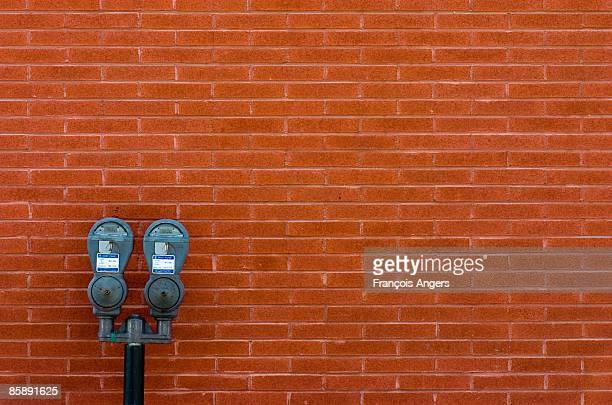 Parking meter against brick wall