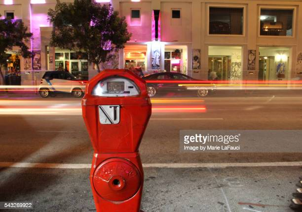 Parking meter with moving cars on Miami street