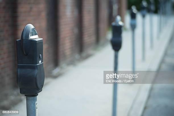 parking meters in row on sidewalk - parking meter stock photos and pictures