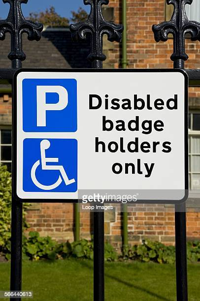 Parking sign displaying 'Disabled badge holders only' on street