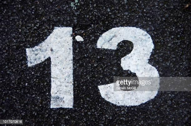 parking spot number 13 stencilled in paint on asphalt in melbourne, victoria, australia - bad luck stock pictures, royalty-free photos & images