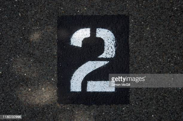 parking spot number 2 stencilled in paint on an asphalt parking lot - number 2 stock pictures, royalty-free photos & images